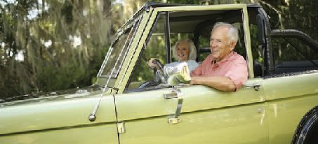 Elderly couple riding in their SUV with the windows down